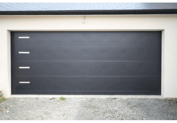 Pose d'une large porte de garage sectionnelle plafond en alu gris anthracite et inserts inox à Avranches (50)