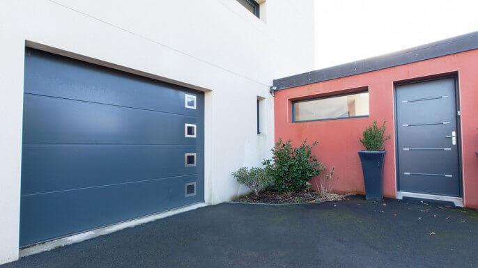 Porte de garage sectionnelle coordonnée avec la porte d'entrée aluminium à La Baule