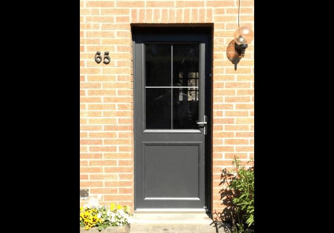 Porte d'entrée en aluminium anthracite au style classique avec grand vitrage et petits bois dans le Nord